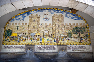 Spain, Catalonia, Barcelona, Drinking water fountain in Portaferrissa Street off La Rambla in the Gothic Quarter with a tiled depiction of one of the gates to the old walled city.,