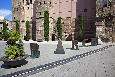 Spain, Catalonia, Barcelona, Scuplture by Joan Brossa in front of Barcelonas Roman wall, where the aqueduct once entered the city and spells out the word Barcino, the Roman name of Barcelona.