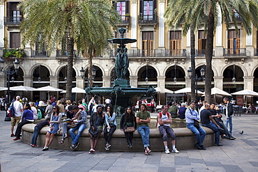 Spain, Catalonia, Barcelona, Tourists sat around the fountain in Placa Reial.