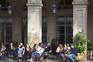 Spain, Catalonia, Barcelona, Tourists sat at tables outside cafe in Placa Reial.