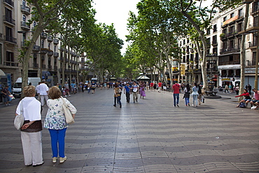 Spain, Catalonia, Barcelona, Tourist walking along the tree lined avenue of La Rambla.