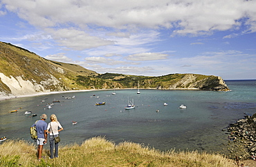England, Dorset, Isle of Purbeck, Couple looking out over Lulworth Cove and Jurassic Coast.