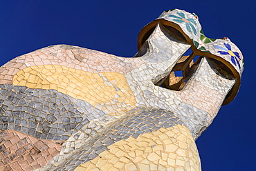 Spain, Catalunya, Barcelona, Antoni Gaudi's Casa Batllo building, colourful chimney pots on the roof terrace.