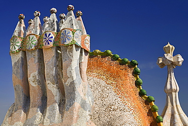 Spain, Catalunya, Barcelona, Antoni Gaudi's Casa Batllo building, colourful chimney pots on the roof terrace with the four armed cross also inclluded.