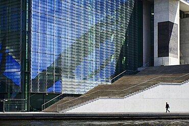 Germany, Berlin, Pedestrian walking along the River Spree in front of Marie Elizabeth Luders Haus.