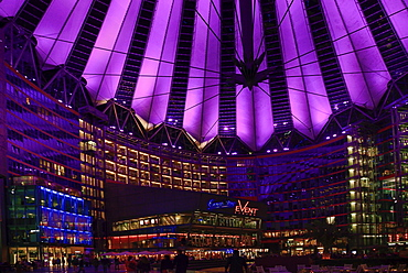 Germany, Berlin, Potzdamer Platz, Sony Centre with glass canopied roof over central plaza at night.