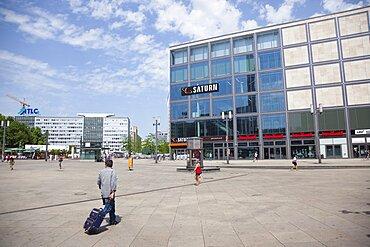 Germany, Berlin, Mitte, Tourist crossing Alexanderplatz with luggage.