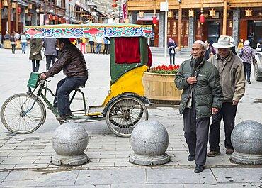 China, Sichuan, Songpan, Yawning trishaw driver and walking aged citizens.