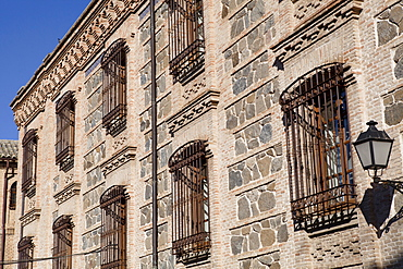 Spain, Castilla La Mancha, Toldeo, Bars and grills to windows on old town houses.