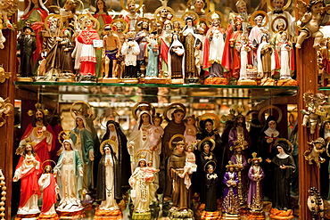 Spain, Madrid, Religious statues and icons on display in shop window.
