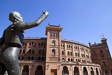 Spain, Madrid, Statue of a matador with the Plaza de Toros de las Ventas in the background.