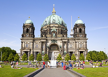 Germany, Berlin, Mitte, Museum Island. Berliner Dom, Berlin Cathedral. people cooling down in a fountain in Lustgarten in front of the church with copper green domes and the Fernsehturm TV Tower beyond.