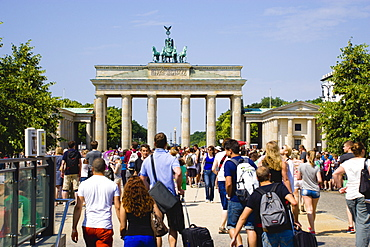 Germany, Berlin, Mitte, sightseeing tourists emerging from the U-Bahn and S-Bahn station on Unter den Linden and walking towards Brandenburg Gate or Brandenburger Tor.
