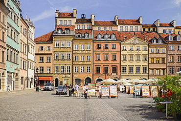 Poland, Warsaw, Stare Miasto or Old Town Square, Colourful facades of buildings on the north side of the square with open air restaurant and artwork on display.