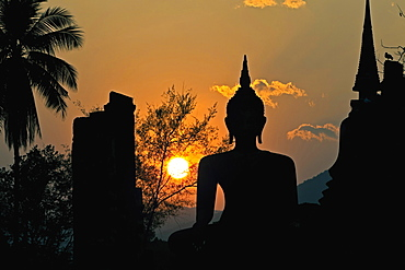Thailand, Sukothai, Seated Buddha and stupa silhouetted against the setting sun, Wat Mahathat Royal Temple.