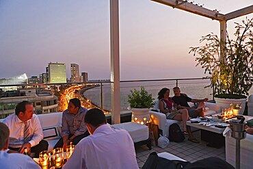 India, Maharashtra, Mumbai, People enjoying a drink at sunset at the rooftop bar of the Intercontinental Hotel on Marine Drive.