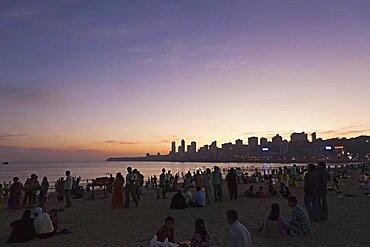 India, Maharashtra, Mumbai, Crowd on Chowpatty Beach at dusk.