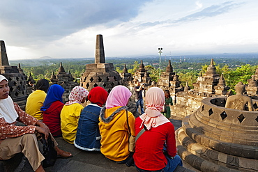 Indonesia, Java, Borobudur, A group of very colourfully dressed, seated Muslim women look out over the monument to the surrounding countryside.