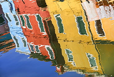 Italy, Veneto, Burano Island, Colourful housing reflected in canal.