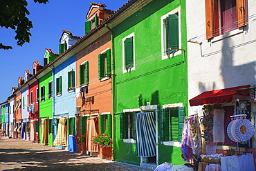 Italy, Veneto, Burano Island, Colourful row of house facades with outdoor display of lace for sale. - 797-12911