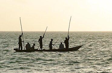 Tanzania, Zanzibar, Fishermen at dawn paddling out to go fishing, close to Paje.