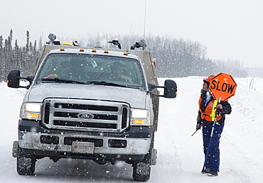 Canada, Alberta, Wabasca, Metis First Nation road flagger directing traffic related to oil and gas activities.
