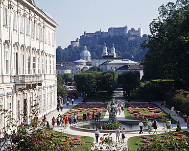 AUSTRIA Salzburg Province Salzburg Mirabell Palace with tourists walking in the formal gardens with Hohensalzburg Fortress on the overlooking hill