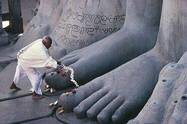 INDIA Karnataka Sravanabelagola Jain puja at feet of seventeen metre high naked statue of Bahubali  the Gomateshvara.  One of the oldest and most important Jain pilgrimage centres in India.   Shravan Belgola