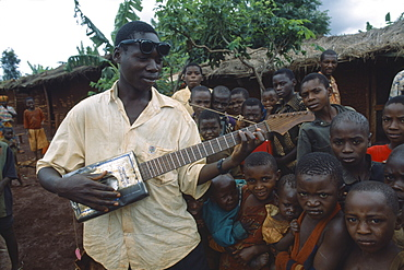 TANZANIA West Great Lakes Region Refugee children listening to boy playing guitar made from cooking oil can.