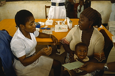 NIGERIA Imo State Medical UNICEF vaccination project.  Female nurse with woman and crying child. Innoculation  injection African Children Female Women Girl Lady Kids Nigerian Western Africa Female Woman Girl Lady