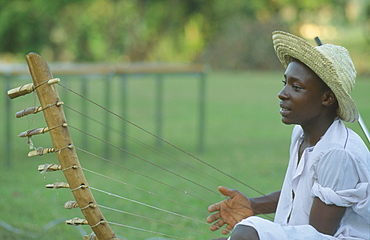 UGANDA  Kampala Folk musician playing harp like instrument.
