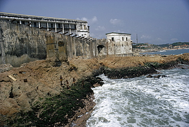 GHANA  Cape Coast Cape Coast Castle.  Line of cannons along seventeenth century castle ramparts with children playing on rocks below. West Africa
