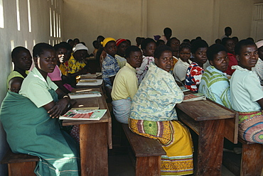 MALAWI  Kunyinda Camp Mozambican refugee women attending adult literacy class. Young woman in foreground with child asleep on her back.