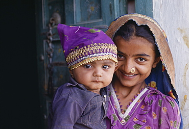 INDIA Gujarat Kutch Dhordo Village.  Girl with nose ring holding young child.