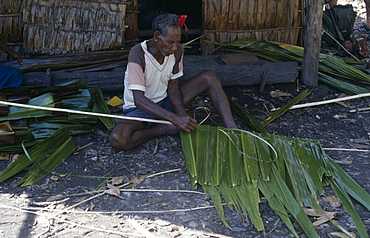 PACIFIC ISLANDS Melanesia Solomon Islands Malaita Province  Lau Lagoon  Foueda Island.  Traditional building methods  man stitching lengths of palm leaves to narrow strip of wood to use in house construction.