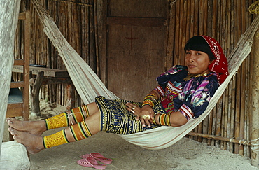 PANAMA San Blas Islands Kuna Indians Young Kuna mother rests in hammock outside home  wearing brightly coloured traditional layered applique mola panel    traditional bead design arm and leg bands and gold nose ring. Cuna Caribbean American Central America Classic Classical Colored Female Women Girl Lady Hispanic Historical Latin America Latino Older Panamanian West Indies