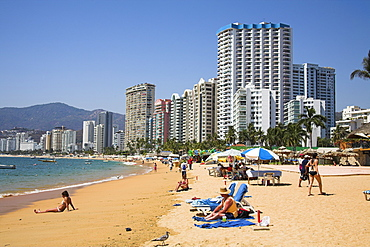 Mexico, Guerrero State Acapulco Condominiums and hotels beside beach  people sunbathing.