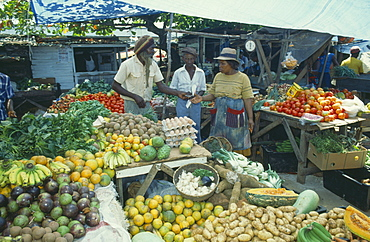 WEST INDIES Jamaica Montego Bay Two women buying fruit from vendor in market