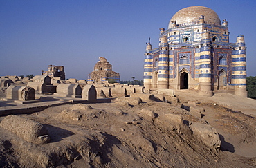 Tomb of Bibi Jawindi with domed roof and two similar crumbling buildings with dusty graveyard in the foreground, Uch Sharif, Pakistan