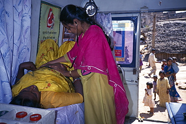 Female health worker examining a pregnant woman in a mobile clinic, Children and woman seen outside through open door, Bangalore, Karnataka, India