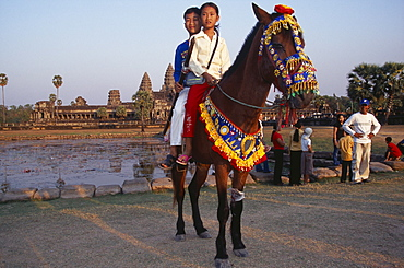 Cambodian children visiting Angkor during the Chinese New Year having photographs taken on pony wearing decorative harness in front of lake and temple complex, Angkor Wat, Siem Reap Province, Cambodia