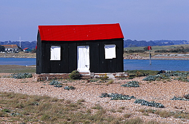 Rye harbour, Red and black corrugated hut with white doors built on the shingle with the harbour inlet behind, Rye, East sussex, England, United Kingdom