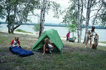 Canadian family on outback holiday setting up camp beside lake, Children with tent and sleeping bag mother with canoe and father using axe to split log, Camping, Canada