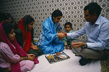 Woman tying thread on wrist of man during the Sacred Thread ceremony, The Hindu male rite of passage ceremony, England, United Kingdom