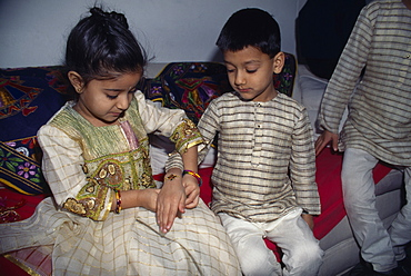 Young girl tying a thread to the wrist of a young boy during the Sacred Thread ceremony, The Hindu male rite of passage ceremony, England, United Kingdom