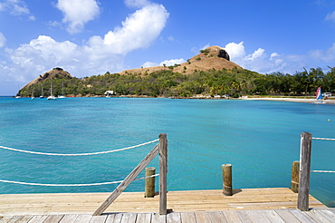 Pigeon Island National Historic Park seen from a nearby wooden jetty with yachts at anchor in Rodney Bay, Gros Islet, St Lucia