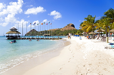 Tourists on the beach at Sandals Grande St Lucian Spa and Beach Resort hotel beside a wooden jetty with Pigeon Island National Historic Park beyond, Gros Islet, St Lucia