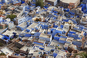Aerial view over flat rooftops of the blue painted houses of the Brahman neighbourhood from Meherangarh Fort known as the Blue City , Jodhpur, Rajasthan, India