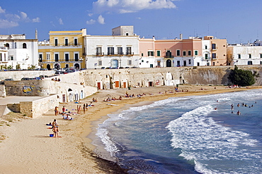 View of old city with traditional houses beside sea wall overlooking curving sandy beach with people sunbathing and swimming, Gallipoli, Puglia, Italy
