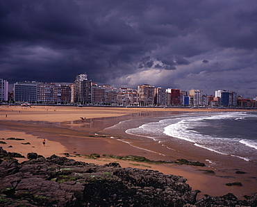 High rise city buildings overlooking beach with people in water on beach and surfing, Grey cloudy sky with approaching storm, Rocks and seaweed in foreground, Gijon, Asturias, Spain